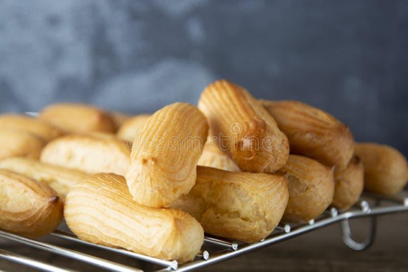 Eclairs o profiterole que se preparan en el molde para el horno Postre francés tradicional Cocinar las galletas hechas en casa, p fotos de archivo libres de regalías