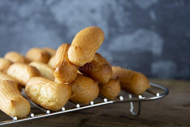 Eclairs o profiterole que se preparan en el molde para el horno Postre francés tradicional Cocinar las galletas hechas en casa, p imagen de archivo libre de regalías
