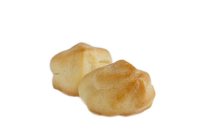 Eclairs o profiterole sabrosos dulces en el fondo blanco Pudín francés de la pasta de azúcar del chocolate Izolated imagen de archivo libre de regalías