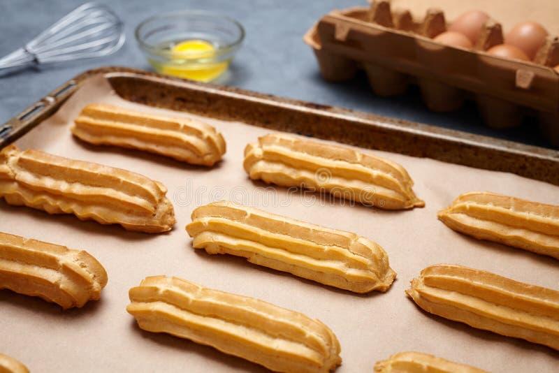 Eclairs o profiterole tradicionales que se preparan con los huevos en el molde para el horno imágenes de archivo libres de regalías
