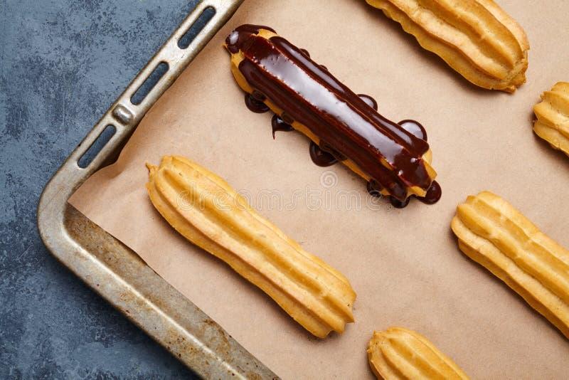 Eclairs o profiteroles con el chocolate y la receta preparada poner crema azotada fotografía de archivo