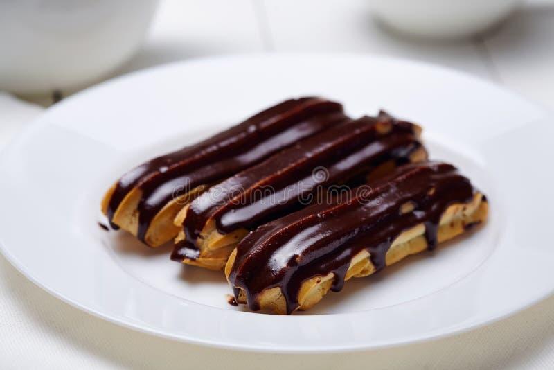 Eclairs o profiteroles con la formación de hielo del chocolate en el plato blanco fotografía de archivo