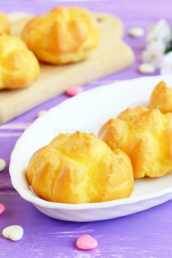 Eclairs o profiteroles dulces sabrosos con crema Diríjase los eclairs hechos llenados de crema de la mantequilla en una placa y u fotografía de archivo