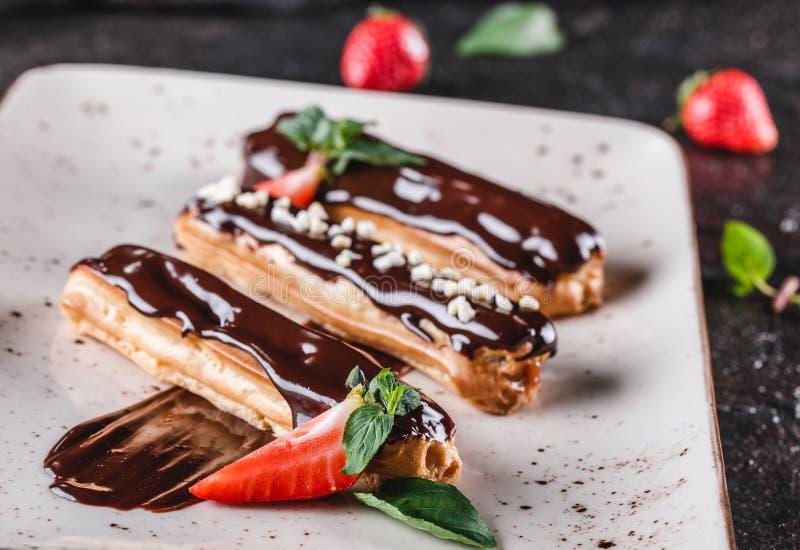 Eclairs o profiteroles hechos en casa de la torta con natillas, chocolate y fresas en el fondo oscuro servido con la taza de caf? imágenes de archivo libres de regalías