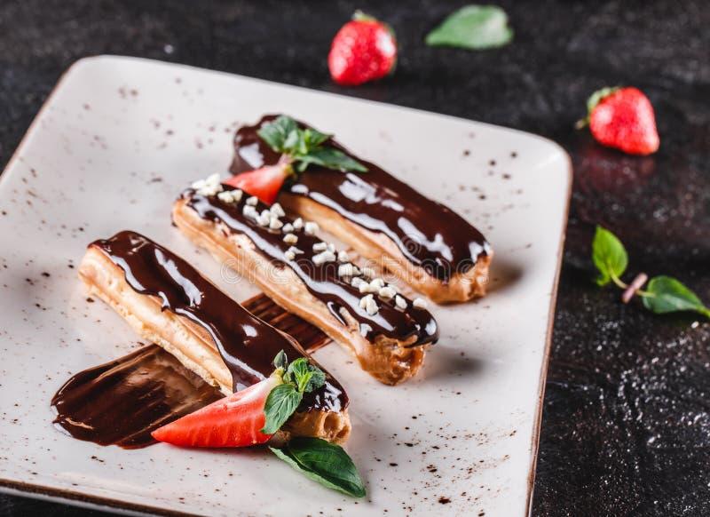 Eclairs o profiteroles hechos en casa de la torta con natillas, chocolate y fresas en el fondo oscuro servido con la taza de caf? fotos de archivo