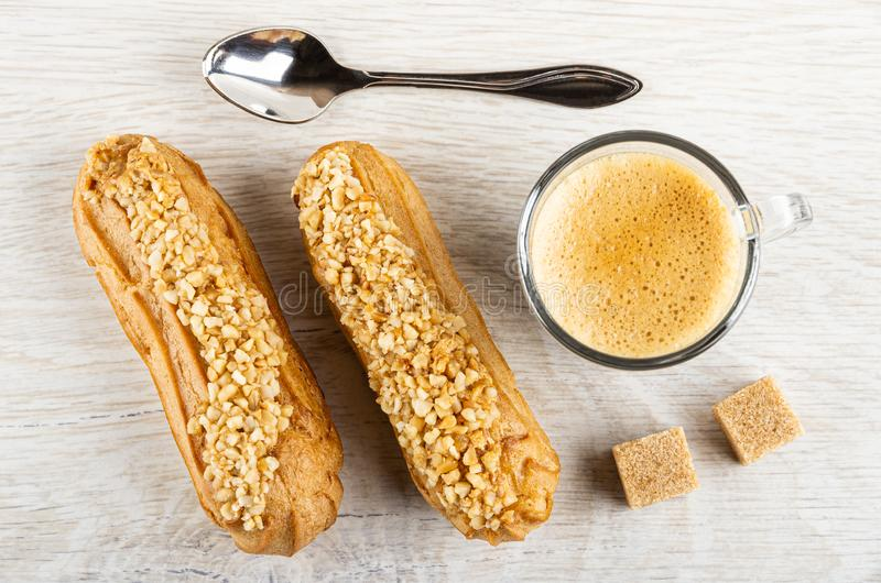 Eclairs with peanut, spoon, cup of espresso, sugar on table. Top view. Eclairs with peanut, spoon, cup of coffee espresso, sugar cubes on wooden table. Top view royalty free stock photography