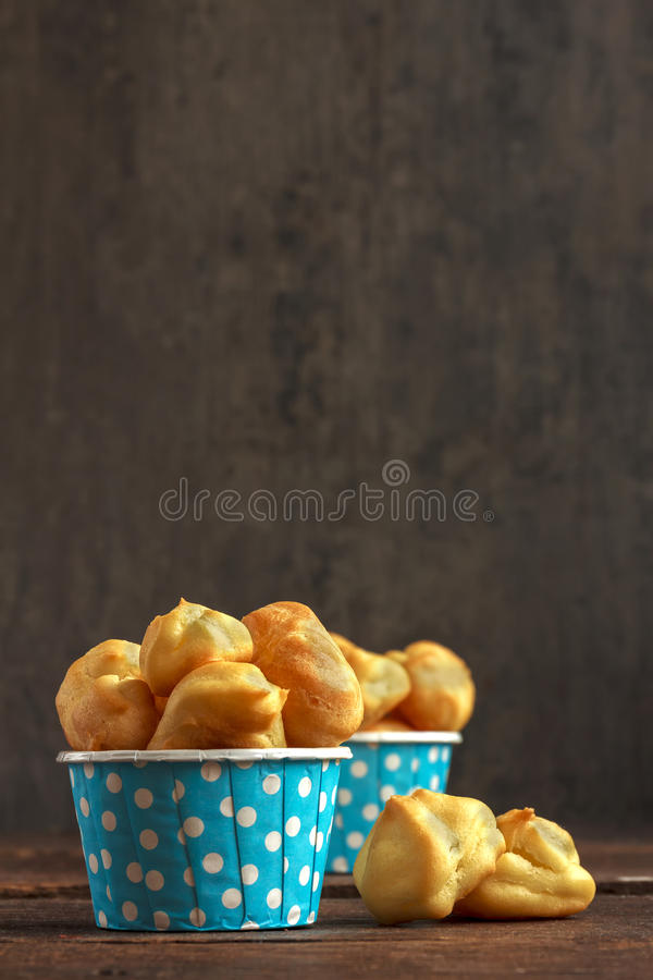 Eclairs or profiterole in blue paper cup on dark background. French dessert. Empty space for design text template. royalty free stock images