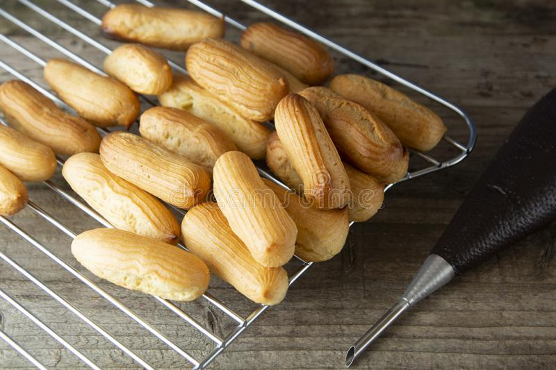 Eclairs or profiterole preparing on baking sheet. Traditional French dessert. Cooking homemade cookies, dessert stock images
