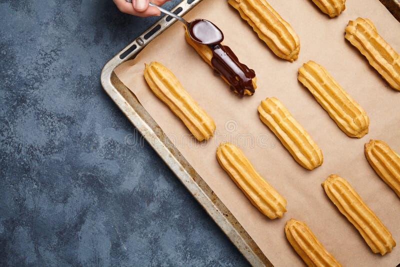 Eclairs, profiterole que se prepara en el molde para el horno, chocolate de extensión con la cuchara fotos de archivo