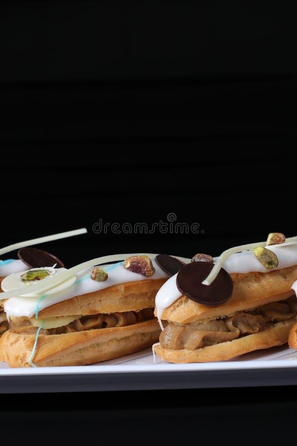 Eclairs riempiti di crema condita e ghiacciati con i pistacchi ed il cioccolato fotografia stock