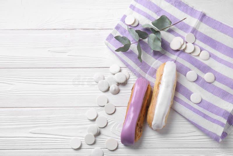 Eclairs saborosos com os pedaços de chocolate brancos na tabela de madeira foto de stock royalty free