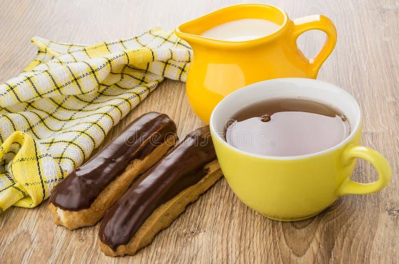 Eclairs, thé dans la tasse, cruche de lait, serviette à carreaux image libre de droits