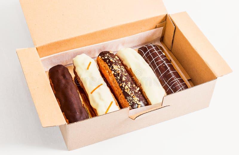 Eclairs, tortas en un cartón en un fondo blanco fotografía de archivo