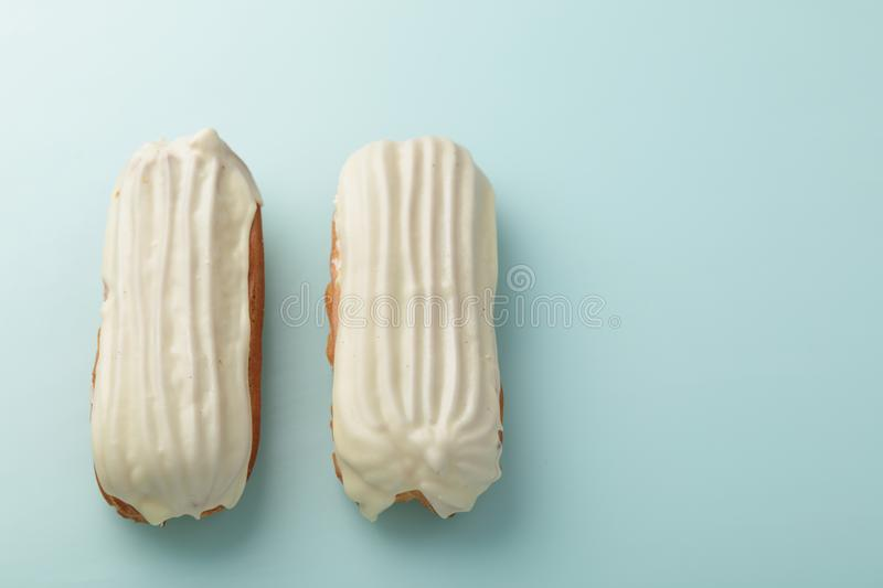 Eclairs with White Chocolate Glaze on duck egg blue background royalty free stock photos