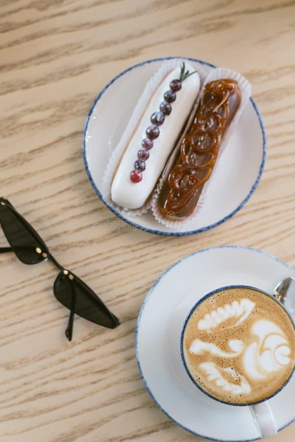 eclairs y café franceses dulces deliciosos en una cafetería Desayuno de la mañana en una tabla ligera de una chica joven foto de archivo libre de regalías