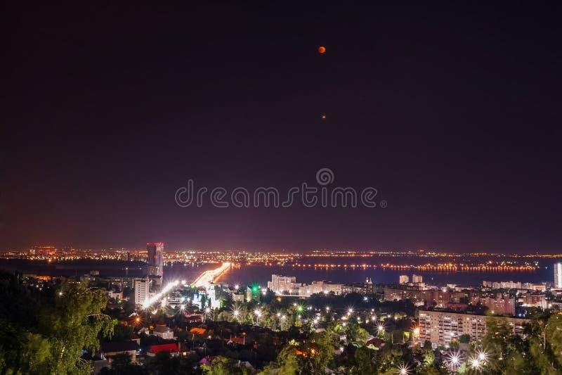 Eclipse da lua Vista da cidade da noite de Saratov, Rússia As luzes de uma metrópole na noite fotografia de stock royalty free