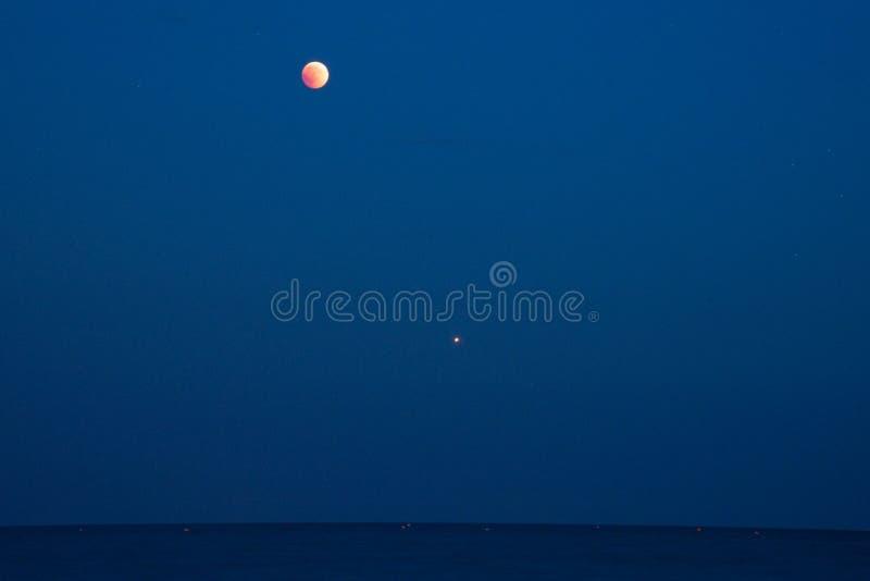 Eclipse de la luna, visible el planeta Marte, perfil del mar imagen de archivo libre de regalías