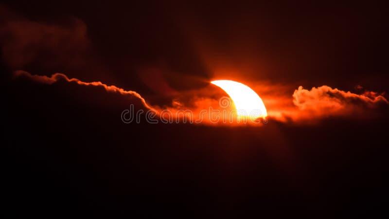 Eclissi solare dietro le nuvole fotografia stock