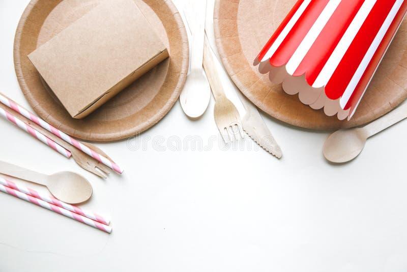 Eco友好的一次性盘在白色大理石背景做了纸 被装饰的匙子,叉子,刀子,有纸杯的板材 免版税库存照片