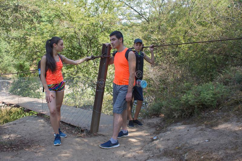 Eco旅游业和健康生活方式概念 有背包的年轻远足者女孩末端男孩 旅客,在度假读地图的远足者 图库摄影
