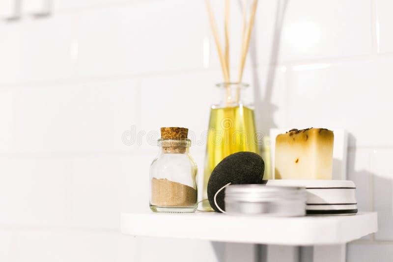Eco自然香波、魔芋的海绵、芬芳油、肥皂和ayurveda ubtan粉末在玻璃在木架子在卫生间,塑料里 库存图片