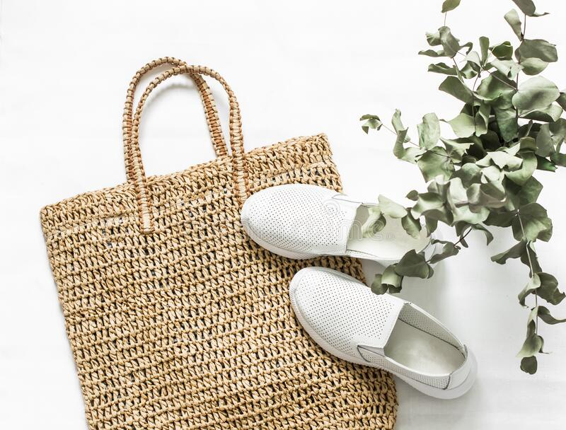 Eco bag made of straw, sport shoes on a white background, top view. Shopping walking concept.  stock photography