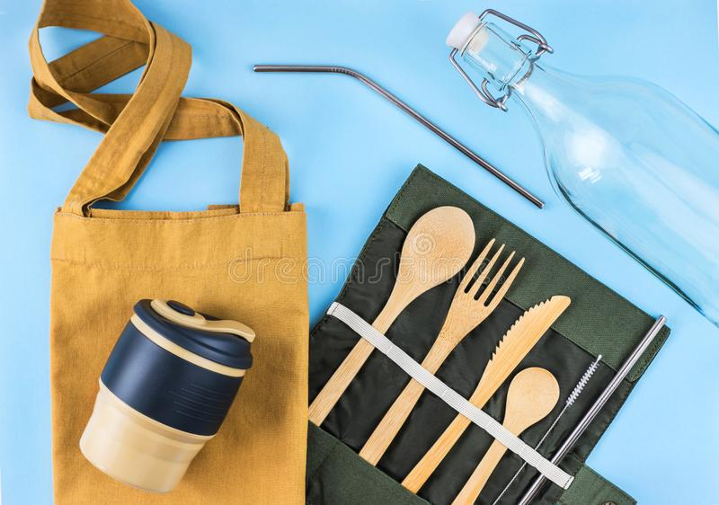 Eco bags with bamboo cutlery, reusable coffee mug and water bottle. Eco bags with bamboo cutlery, reusable coffee mug and water bottle on blue background stock photo
