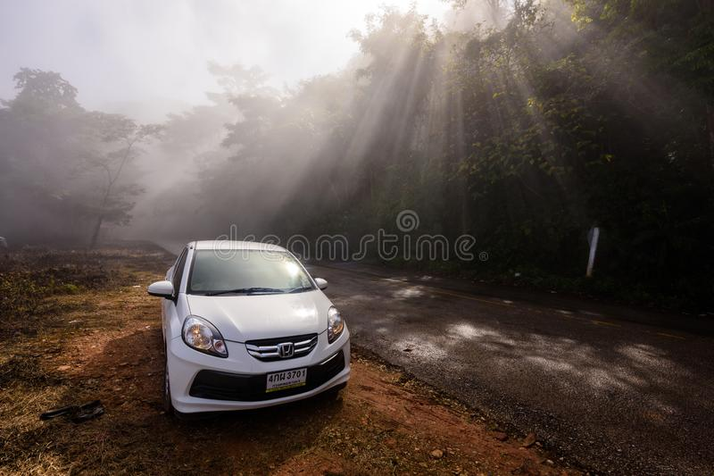 Eco car for road trip at forest. Chiang Rai, Thailand - January 07, 2017: Honda Brio eco car rental parking at mountain uphill road with forest, heavy mist, and royalty free stock photography