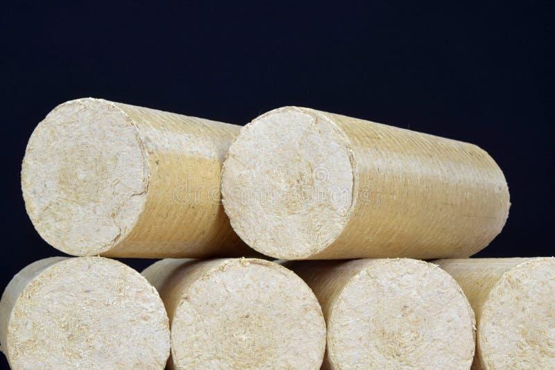 Eco-carvões amassados de madeira endireitados, fundo preto da serragem Combustível alternativo, bio combustível fotografia de stock