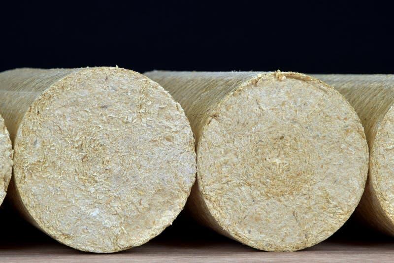 Eco-carvões amassados de madeira endireitados, fundo preto da serragem Combustível alternativo, bio combustível imagem de stock royalty free