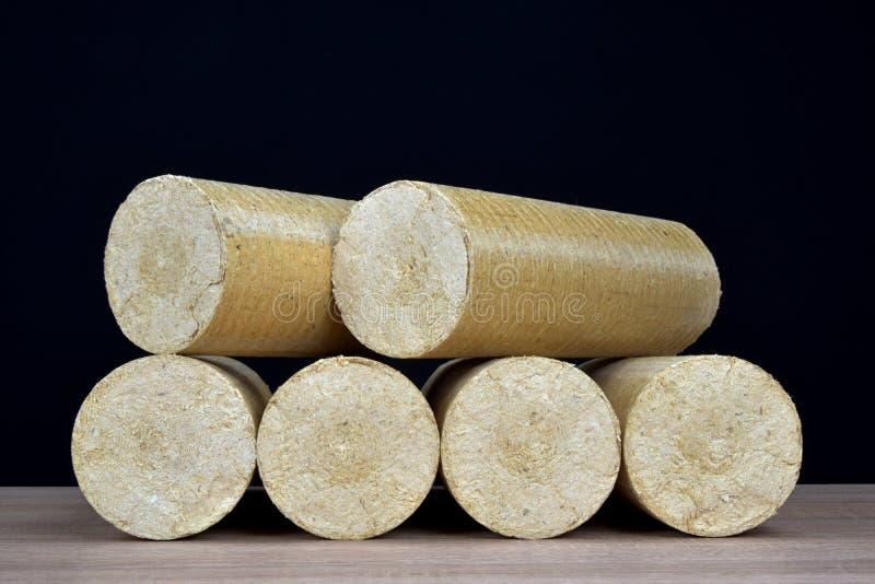 Eco-carvões amassados de madeira endireitados, fundo preto da serragem Combustível alternativo, bio combustível foto de stock royalty free