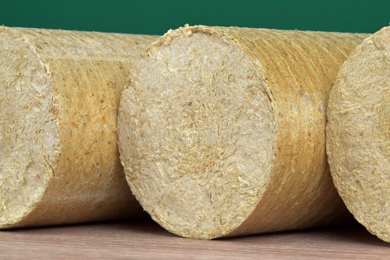 Eco-carvões amassados de madeira endireitados, fundo verde da serragem Combustível alternativo, bio combustível foto de stock royalty free