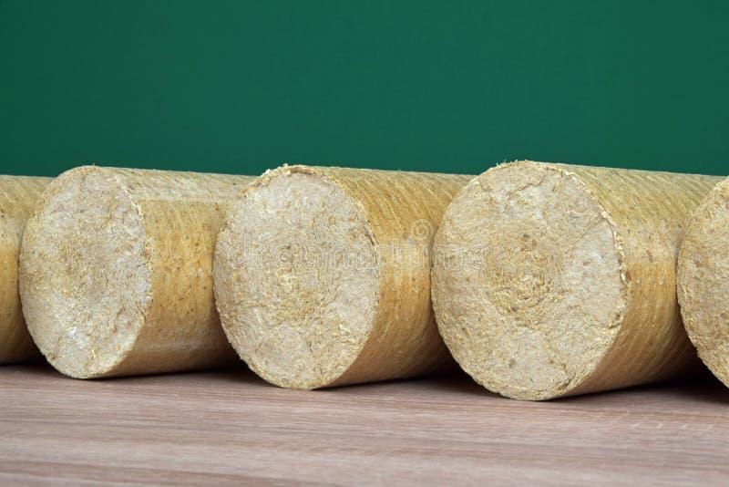 Eco-carvões amassados de madeira endireitados, fundo verde da serragem Combustível alternativo, bio combustível imagem de stock