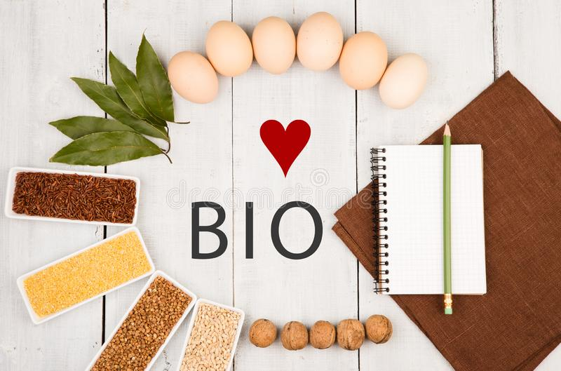 Eco cereals in bowls - text Love Bio, corn grits, brown buckwheat, red rice, pearl barley, eggs, bay leaf laid stock photography