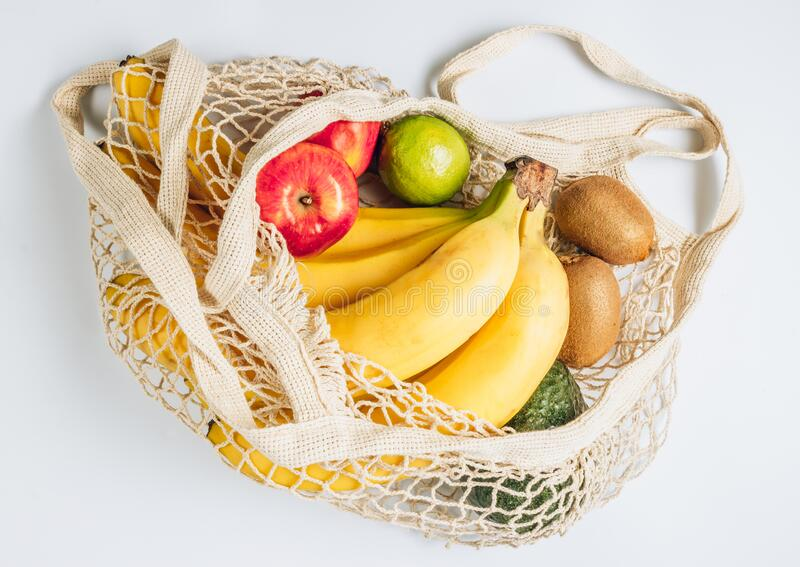 Eco cotton string mesh bag with fruits. Bananas, apples, kiwi, lime and avocado. Ecological Zero Waste Food Shopping. Concept. Top view. Flat lay royalty free stock images