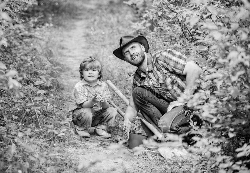 Eco farm. hoe, pot and shovel. Garden equipment. small boy child help father in farming. father and son in cowboy hat on stock image