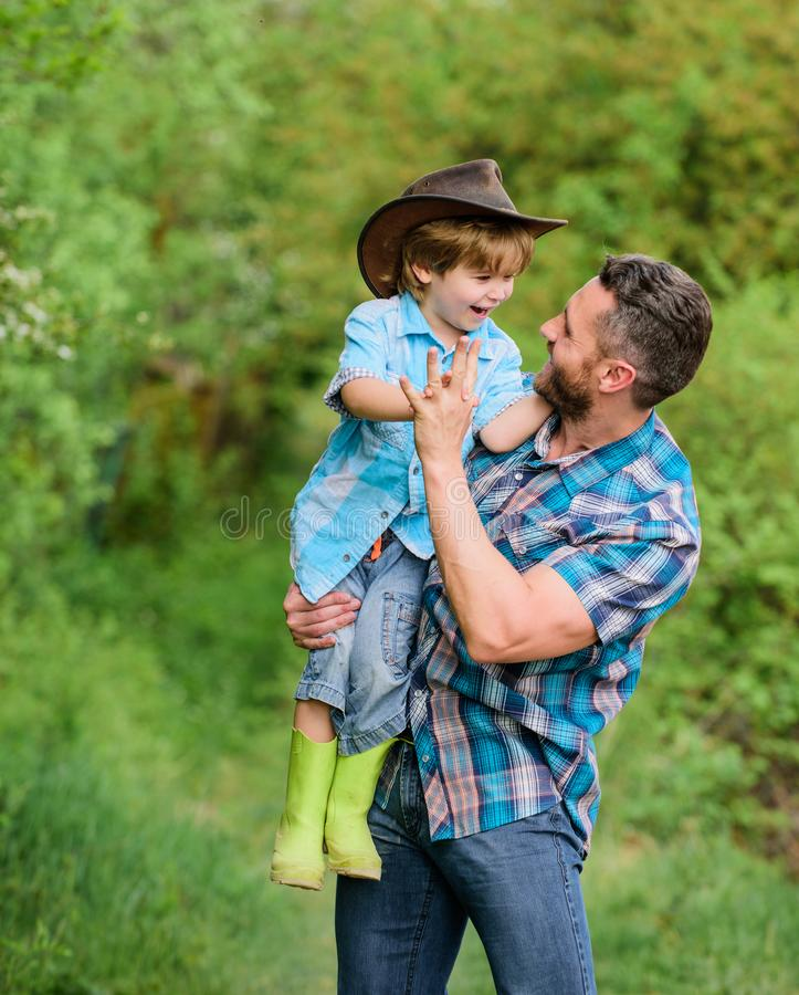Eco farm. small boy child help father in farming. father and son in cowboy hat on ranch. kid in rubber boots. happy man royalty free stock photography