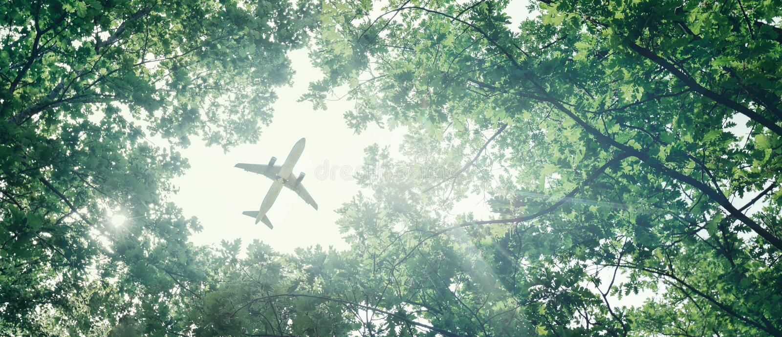 Eco-friendly air transport concept. The plane flies in the sky against the background of green trees. Environmental pollution. Harmful emissions stock photography