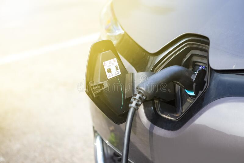 Eco-Friendly Alternative Energy Concept. Electric Car or EV Car Charging At Station With Power Cable Plugged In. Horizontal Image stock images