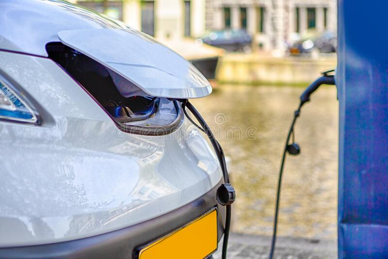 Eco-Friendly Alternative Energy Concept. Electric Car or EV Car Charging At Station With Power Cable Plugged In. Horizontal Image royalty free stock photos
