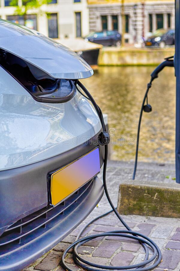 Eco-Friendly Alternative Energy Concept. Electric Car or EV Car Charging At Station With Power Cable Plugged In. Vertical Image stock images