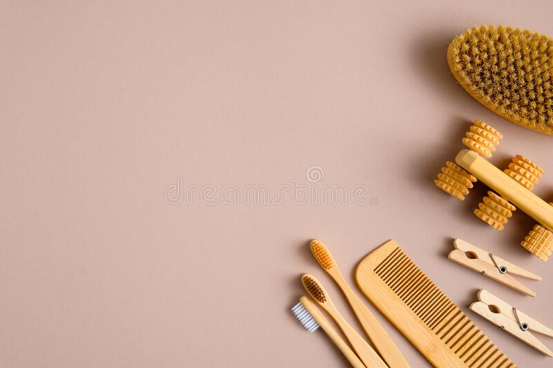 Eco friendly bathroom accessories on brown background. Flat lay biodegradable toothbrushes, wooden hair comb, bath massage brush. Top view with copy space royalty free stock photo