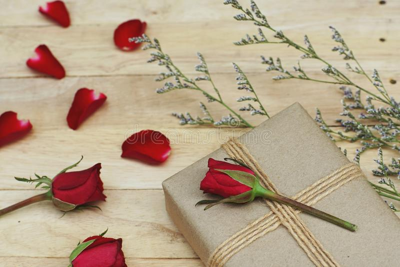 Eco friendly brown paper wrapped gift box present decorated with rose and other flowers on wooden background, valentine ornamental stock image