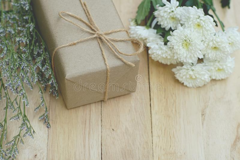 Eco friendly brown paper wrapped gift box present decorated with rose and other flowers on wooden background, valentine ornamental royalty free stock photography