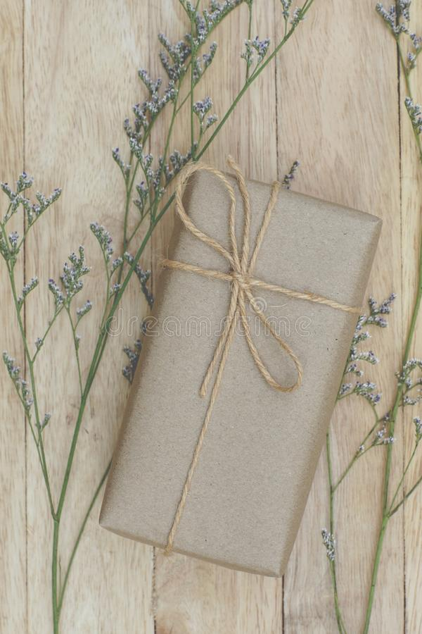 Eco friendly brown paper wrapped gift box present decorated with rose and other flowers on wooden background, valentine ornamental. Concept, copy space stock photography
