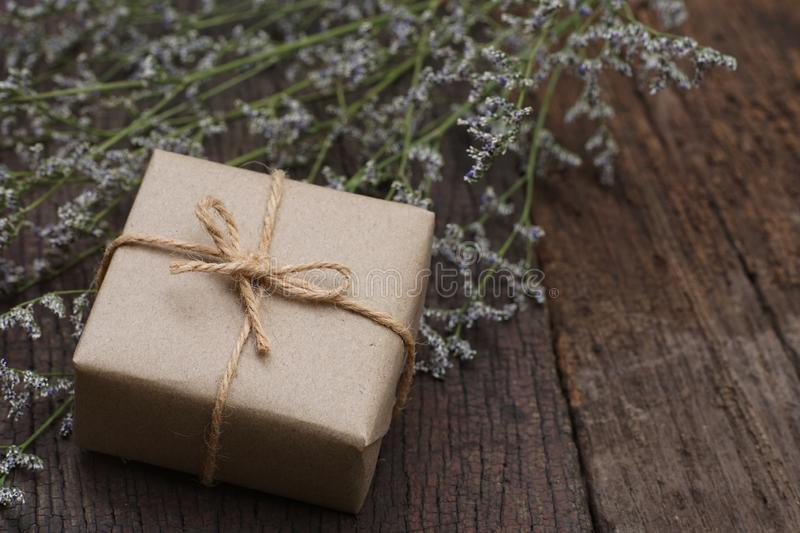 Eco friendly brown paper wrapped gift box present decorated with rose and other flowers on wooden background, valentine ornamental. Concept, copy space stock images