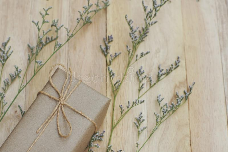 Eco friendly brown paper wrapped gift box present decorated with rose and other flowers on wooden background, valentine ornamental. Concept, copy space royalty free stock photos