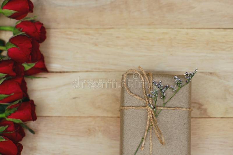Eco friendly brown paper wrapped gift box present decorated with rose and other flowers on wooden background, valentine ornamental. Concept, copy space royalty free stock image