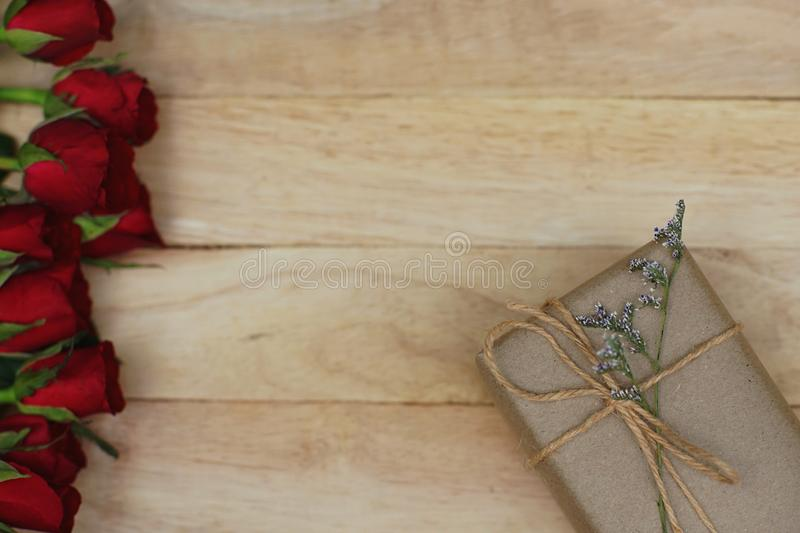 Eco friendly brown paper wrapped gift box present decorated with rose and other flowers on wooden background, valentine ornamental. Concept, copy space stock image