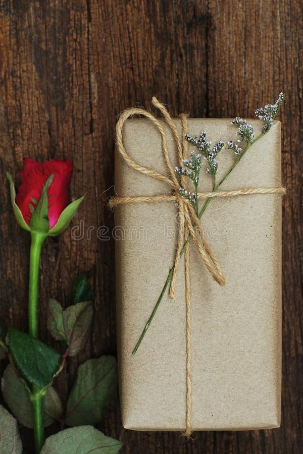 Eco friendly brown paper wrapped gift box present decorated with rose and other flowers on wooden background, valentine ornamental stock photography